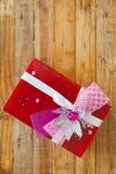 Boîte-cadeau rouge et coeur de ruban et mini rouge à l'intérieur sur le backgr en bois Images stock
