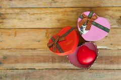 Boîte-cadeau rouge et coeur de ruban et mini rouge à l'intérieur sur le backgr en bois Photos libres de droits
