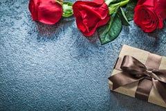 Boîte-cadeau rouge naturel de boutons de rose sur le conce noir de vacances de fond Image libre de droits