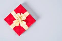 Boîte-cadeau rouge sur le fond gris de couleur Photos libres de droits