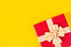 Boîte-cadeau rouge sur le fond jaune de couleur Photos stock