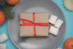 Boîte-cadeau, ruban rouge avec les guimauves, cadeaux de Noël, sur un Tableau bleu sur Gray Plate, vue supérieure photo libre de droits