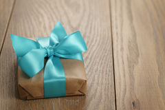 Boîte-cadeau rustique de papier de métier avec l'arc de ruban bleu sur la table en bois Images stock
