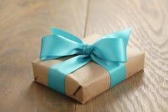 Boîte-cadeau rustique de papier de métier avec l'arc de ruban bleu sur la table en bois Photos stock