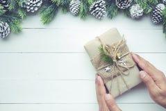 Boîte-cadeau se tenant masculin de cadeaux de Noël dans le style diy de travail manuel Photographie stock