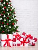 Boîte-cadeau sous l'arbre de Noël décoré avec les boules colorées OV Photographie stock