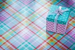 Boîte-cadeau sur le concept vérifié de vacances de fond de tissu Photographie stock libre de droits