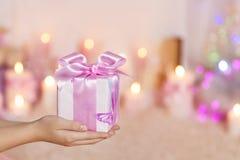 Boîte-cadeau sur les mains, la main femelle et le présent avec l'arc rose au-dessus de Ho Images libres de droits