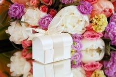 Boîte-cadeau sur un fond d'un bouquet des fleurs Photos libres de droits