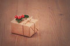 Boîte-cadeau toutes les fois avec des baies de houx sur le fond en bois, modifié la tonalité Photo libre de droits