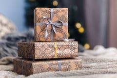 Boîte-cadeau trois au-dessus de plan rapproché beige de lit Ruban pourpre d'arbre de Noël et papier beige Images libres de droits