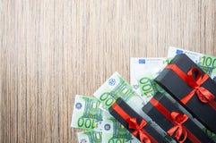 Boîte-cadeau trois noir avec un arc avec d'euro billets de banque sur une table en bois Vue supérieure, l'espace de copie image stock
