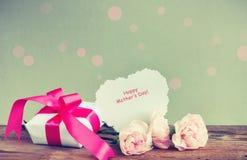 Boîte-cadeau, trois oeillets roses, note de papier Photo libre de droits