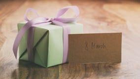 Boîte-cadeau vert avec l'arc pourpre de ruban sur la vieille table en bois avec la carte du 8 mars Photos libres de droits
