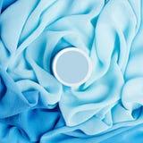 Boîte crème de beauté au-dessus de tissu de turquoise Image libre de droits