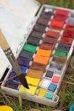 Boîte d'aquarelles avec une brosse sur l'herbe Peinture extérieure avec les peintures et la brosse photos libres de droits