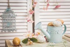 Boîte d'arrosage avec des oeufs de pâques sur un fond rustique en bois Images stock