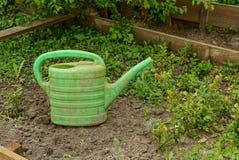 Boîte d'arrosage en plastique sale verte sur l'herbe et la terre photos stock