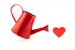 Boîte d'arrosage rouge d'isolement avec le coeur rouge sur le fond blanc Images libres de droits