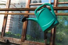 Boîte d'arrosage verte accrochant en serre chaude en bois avec des vitraux photo libre de droits