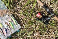 Boîte d'articles de pêche et mensonge de rotation au sol Fond extérieur Images stock