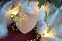 Boîte d'or de présent de coeur avec l'éclairage sur le fond blanc Photographie stock libre de droits