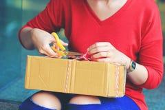 Boîte d'ouverture de jeune femme avec le colis concept à la maison, d'expédition et de service postal photos libres de droits