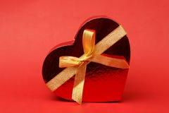 Boîte dans la forme de coeur avec l'arc sur le fond rouge Photographie stock libre de droits