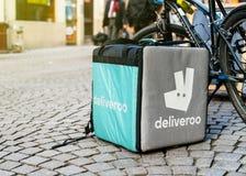 Boîte de cargaison de Deliverro près d'une bicyclette devant le restaurant Image stock