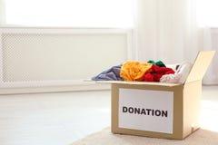 Boîte de carton avec des donations sur le plancher à l'intérieur photo libre de droits