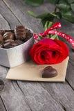 Boîte de chocolats, rose de rouge sur un fond foncé Photos stock