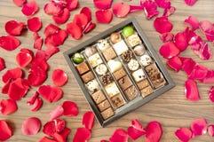 Boîte de chocolats savoureux parmi des pétales de rose - un cadeau romantique Image libre de droits