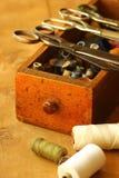 Boîte de couture de vintage avec des ciseaux et des bobines de fil sur la table avec le trou de ver Photos stock