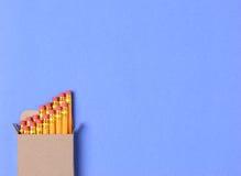 Boîte de crayons sur le bleu Photographie stock libre de droits