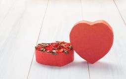 Boîte de forme de coeur avec les roses rouges à l'intérieur sur le dessus de table en bois blanc, L Image libre de droits