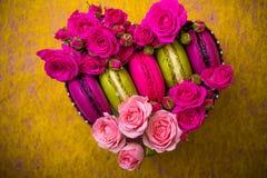 Boîte de forme de coeur avec le fond de macarons de couleur de ressort de rose de baie avec amour Photographie stock