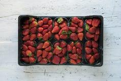 Boîte de fraises parfaites mûres fraîches sur le fond en bois rustique blanc Photo stock