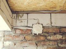 Boîte de jonction électrique blanche sur un mur de briques photographie stock libre de droits