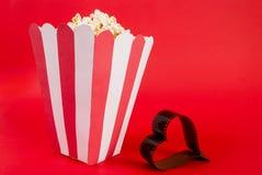 Boîte de maïs éclaté sur le fond rouge et de film sous forme de coeur avec l'espace pour le texte Image stock