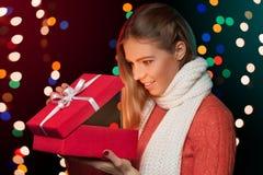 Boîte de Noël heureuse d'ouverture de fille qui rougeoie à l'intérieur Cadeau de Noël image libre de droits