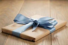 Boîte de papier brune de cadeau fait main avec l'arc de ruban bleu sur la table en bois Photos libres de droits
