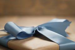 Boîte de papier brune de cadeau fait main avec l'arc de ruban bleu sur la table en bois Photo stock