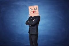 Boîte de port de carton d'homme d'affaires avec le visage fâché peint montrant la langue là-dessus Photographie stock