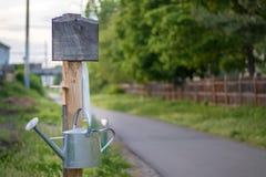 Boîte de signe et d'arrosage à la ferme de la communauté photographie stock