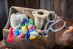 Boîte en bois avec les ciseaux, l'aiguille et les fils Photo stock