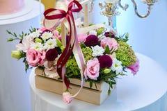 Boîte en bois avec les fleurs de rose, pourpres et jaunes images libres de droits