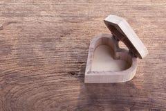 Boîte en bois brune de coeur sur le fond en bois, amour abstrait Image libre de droits