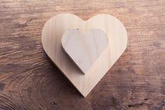 Boîte en bois brune de coeur sur le fond en bois, amour abstrait Photos stock