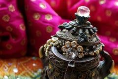 Boîte en bois de cercueil avec les éléphants orientaux de modèles pleins des bijoux d'or sur le fond de tissu de framboise photo libre de droits