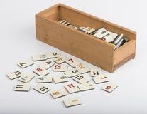 Boîte en bois de rummikub avec des morceaux, fond blanc photographie stock libre de droits